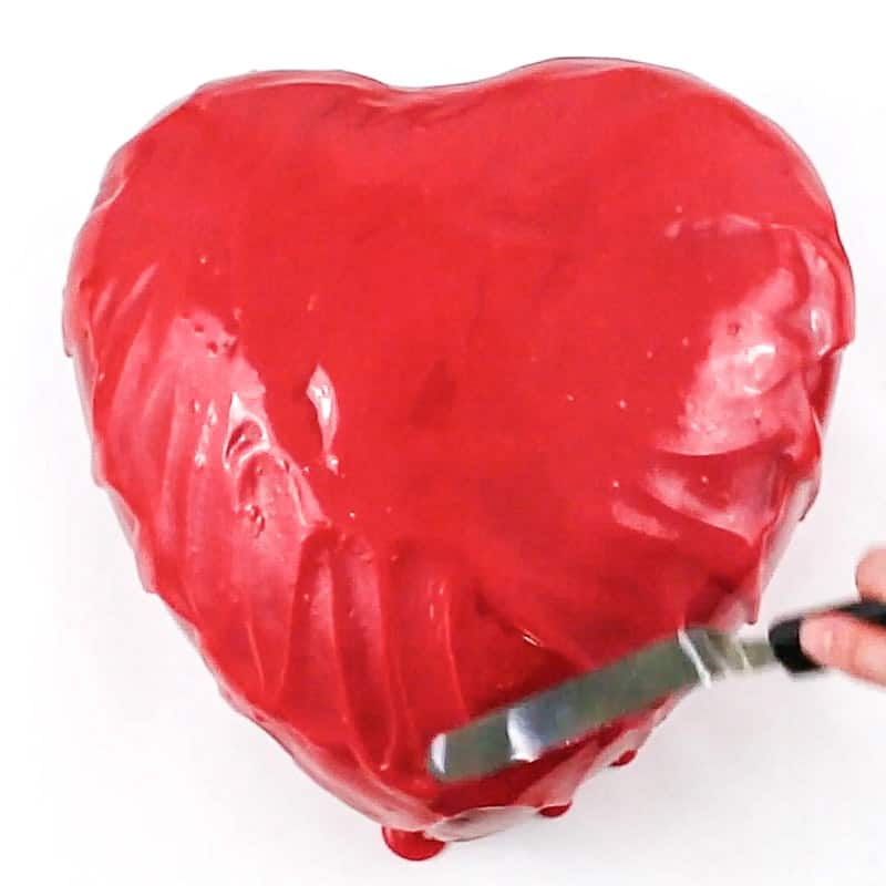 smoothing red ganache on heart cake