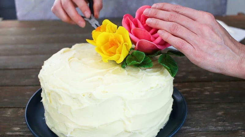 adjusting gumpaste flowers on cake
