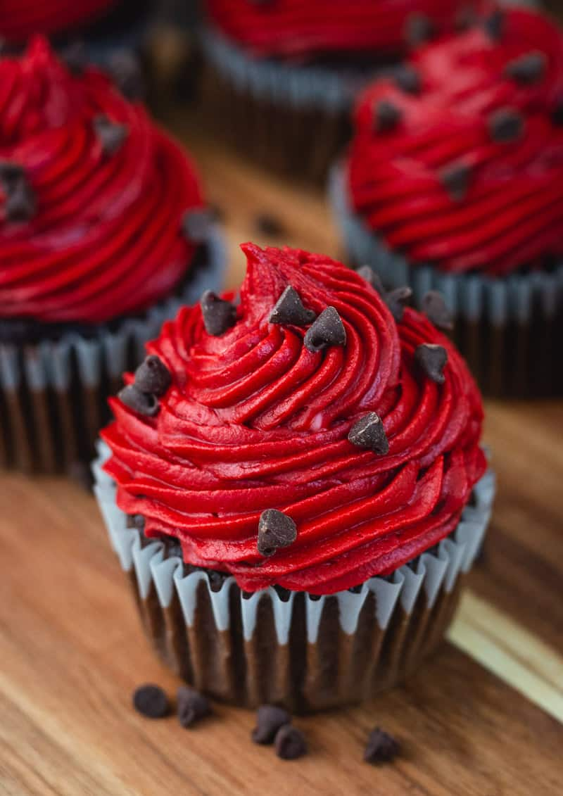 Chocolate cupcakes with red velvet buttercream on a wooden cutting board