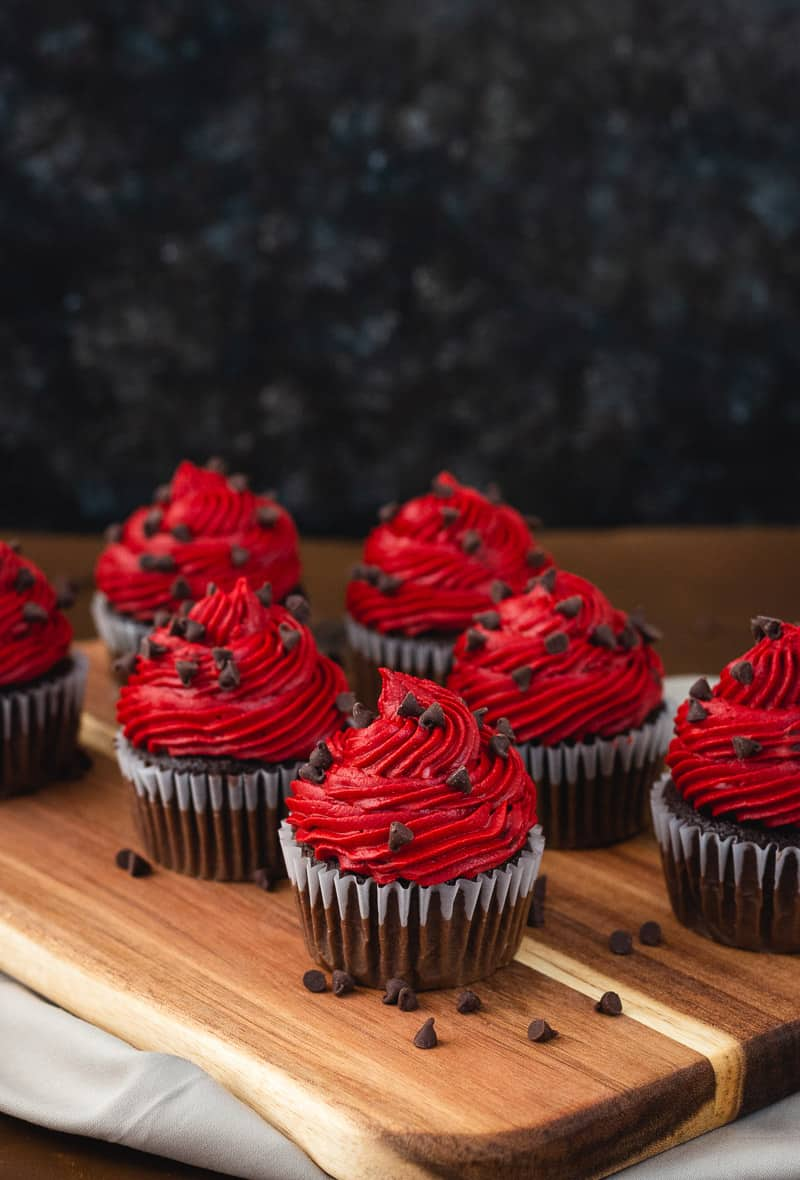 Chocolate cupcakes with red icing on a cutting board