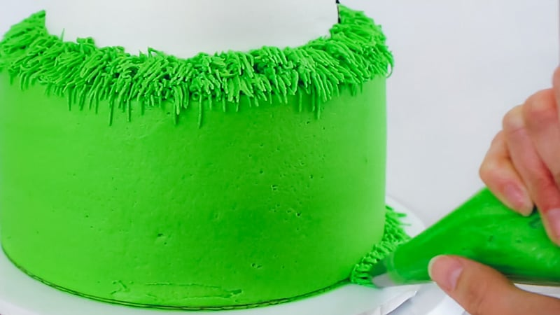 piping buttercream grass along bottom of cake