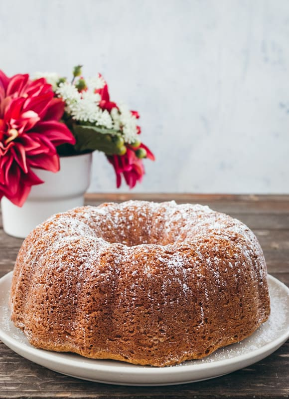 cream cheese bundt cake with powdered sugar on top on a white platter