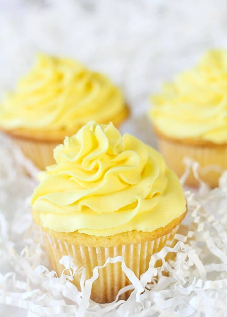 three lemon sour cream cupcakes with lemon buttercream swirls
