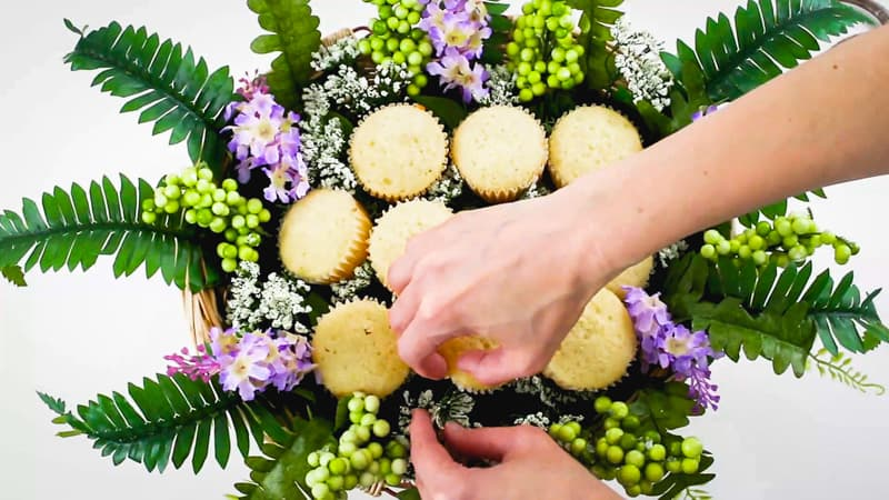 adding small flowers into the cupcake bouquet