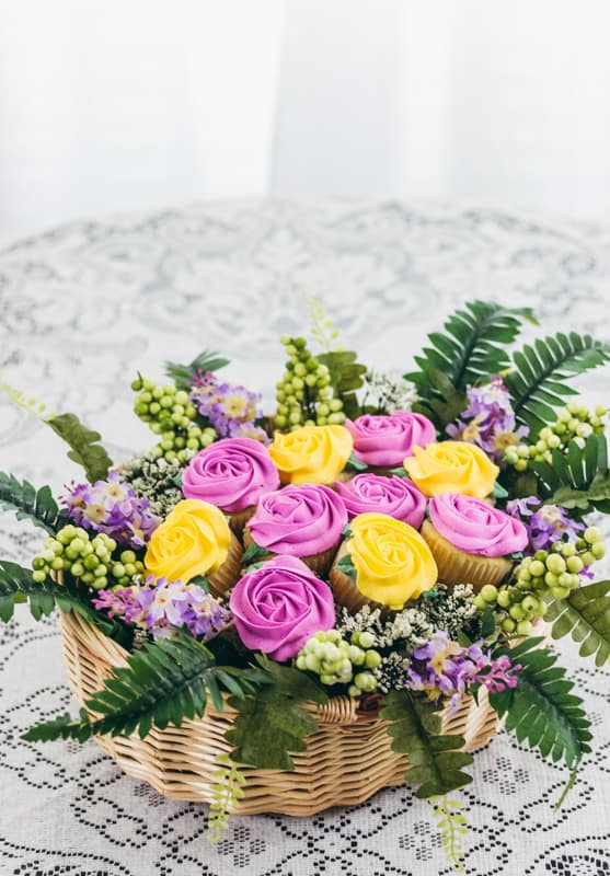 cupcake bouquet in a baset with pink and yellow roses