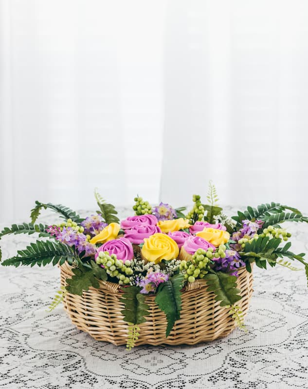 cupcake bouquet in a basket on a lace tablecloth