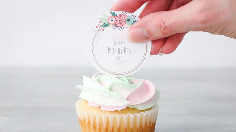 adding cupcake toppers to mothers day cupcakes