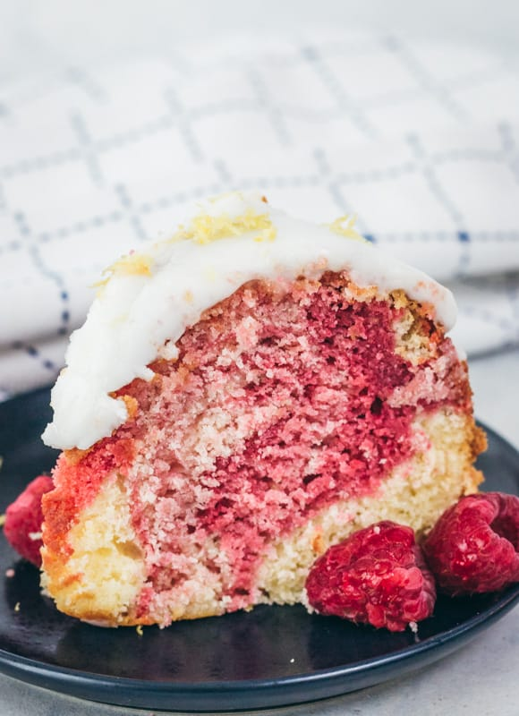 slice of lemon raspberry cake with raspberries on a plate