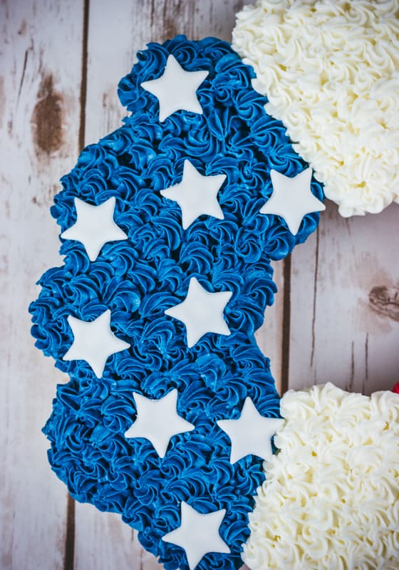 Close up of blue rosettes and white stars on cupcake cake