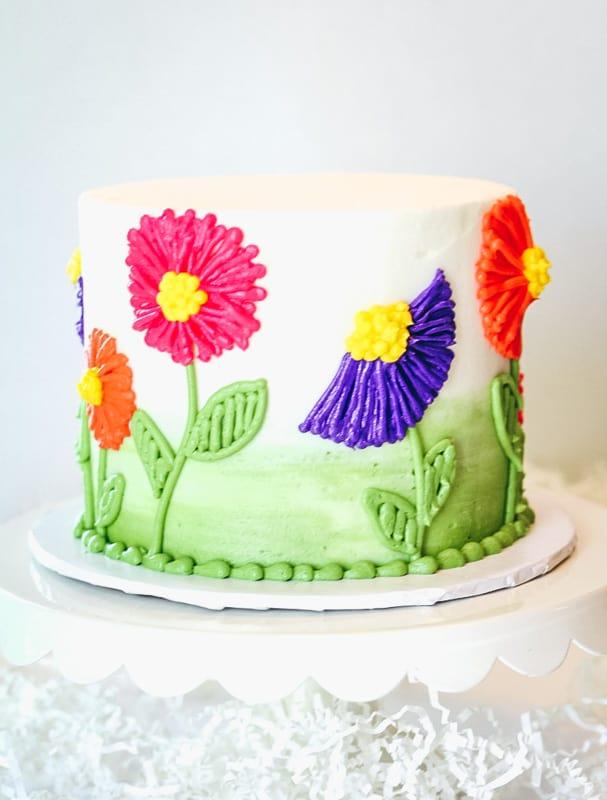 easy buttercream flower cake on a cake stand
