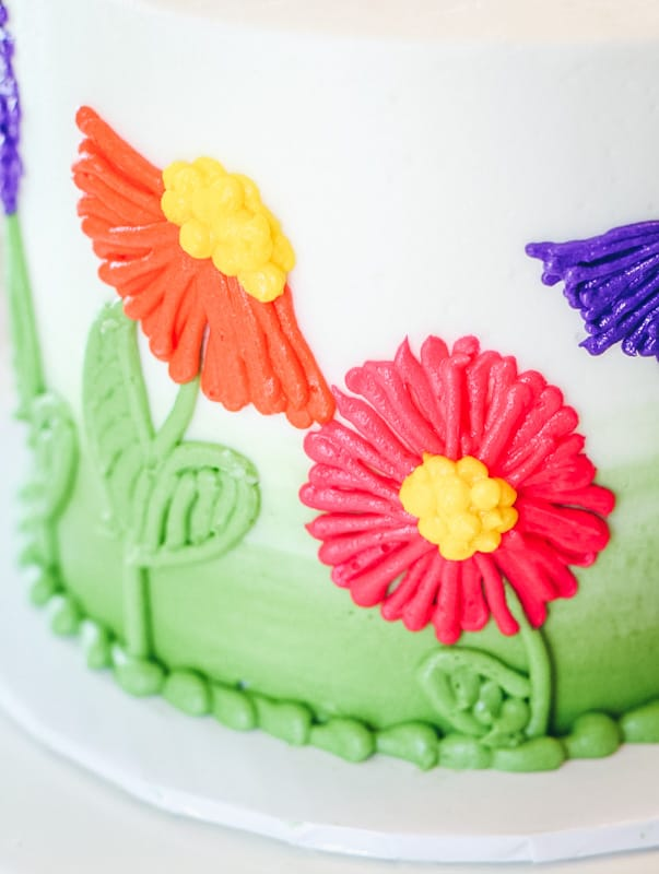 close up of orange and pink flower on cake