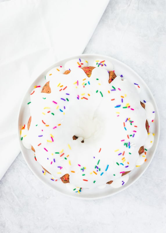 top view of funfetti cake with white glaze and sprinkles