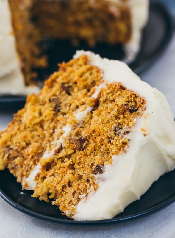 large slice of carrot cake on a plate with icing