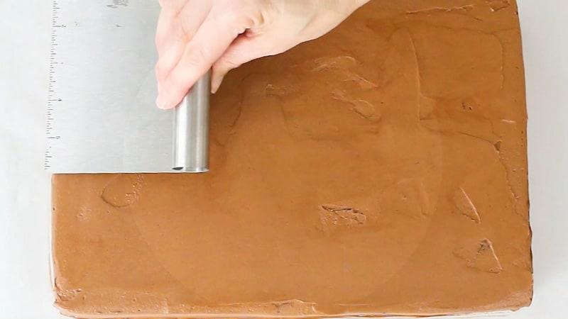 smoothing chocolate buttercream on cake