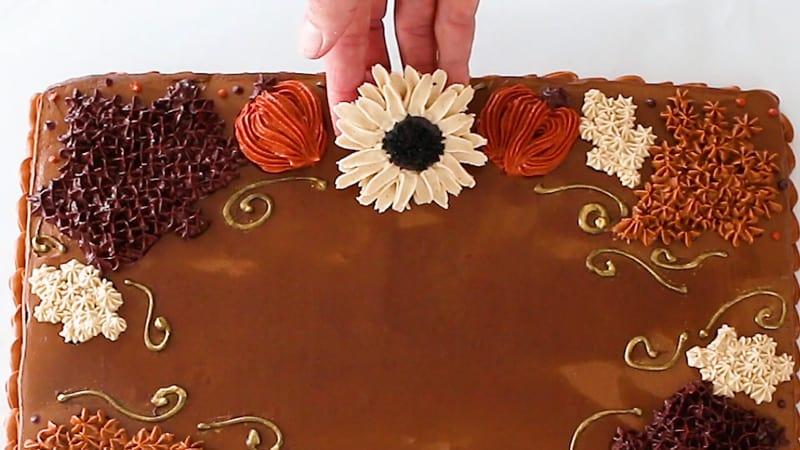 adding cream buttercream sunflower to cake