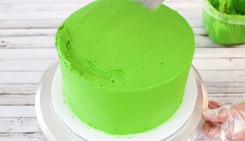 covering cake with green buttercream