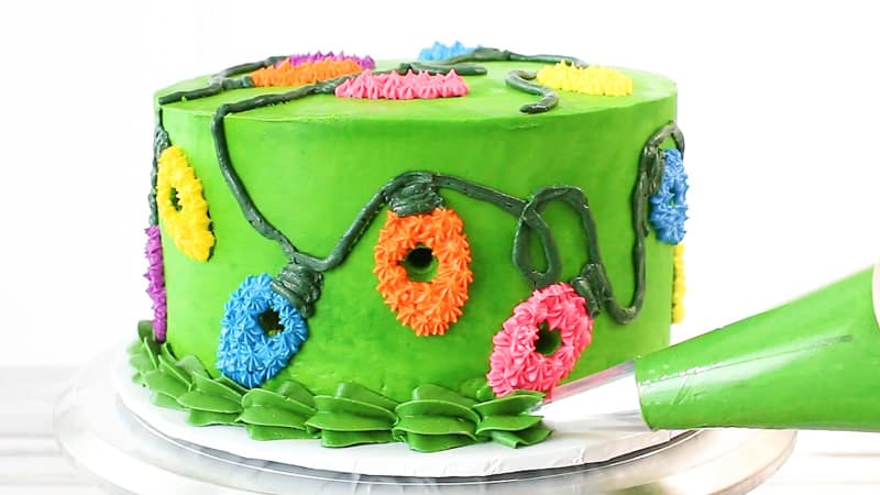 piping large green shell border on cake