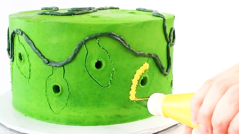 piping buttercream stars onto cake