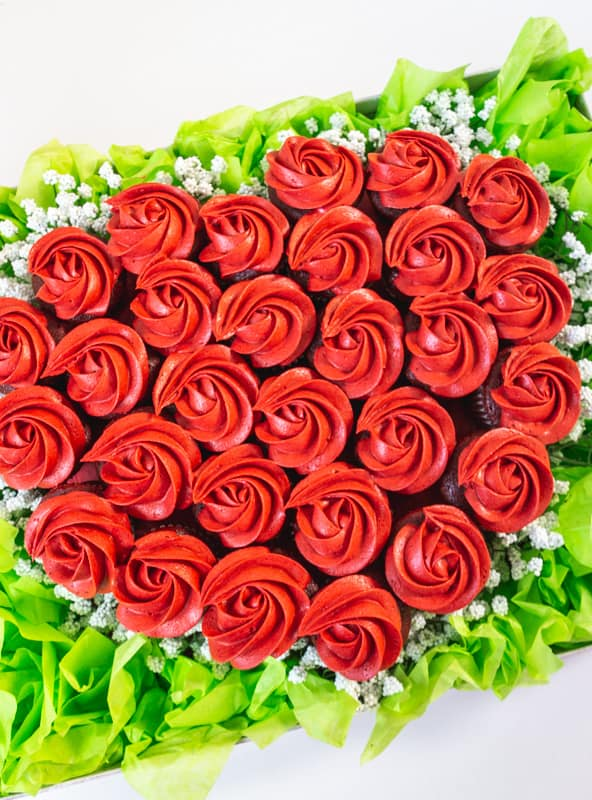 close up of mini cupcakes with red rosettes