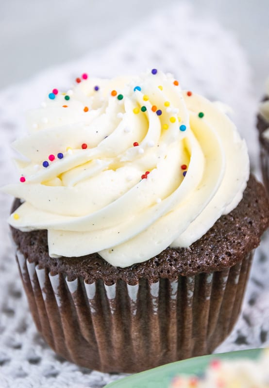 fluffy white icing on a chocolate cupcake with sprinkles