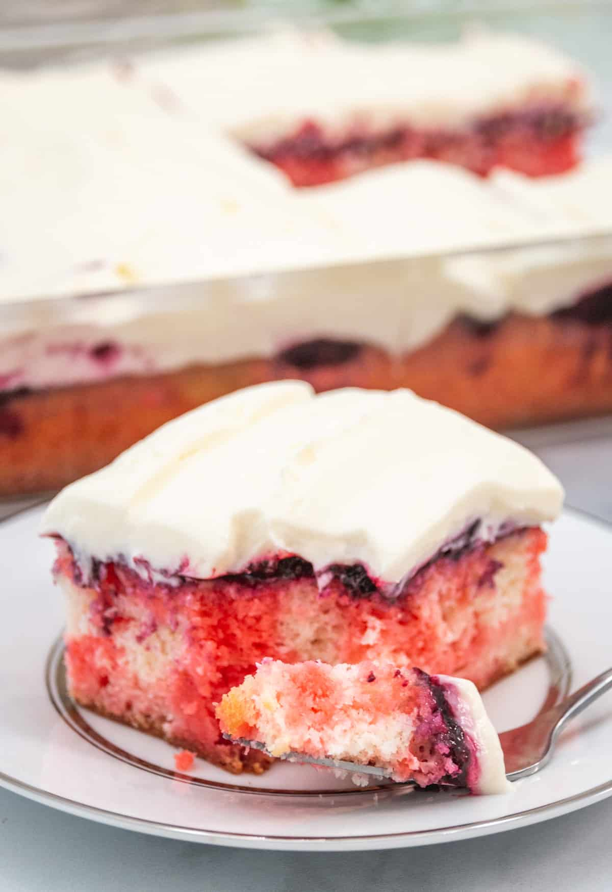 large slice of berry poke cake with fork on a plate