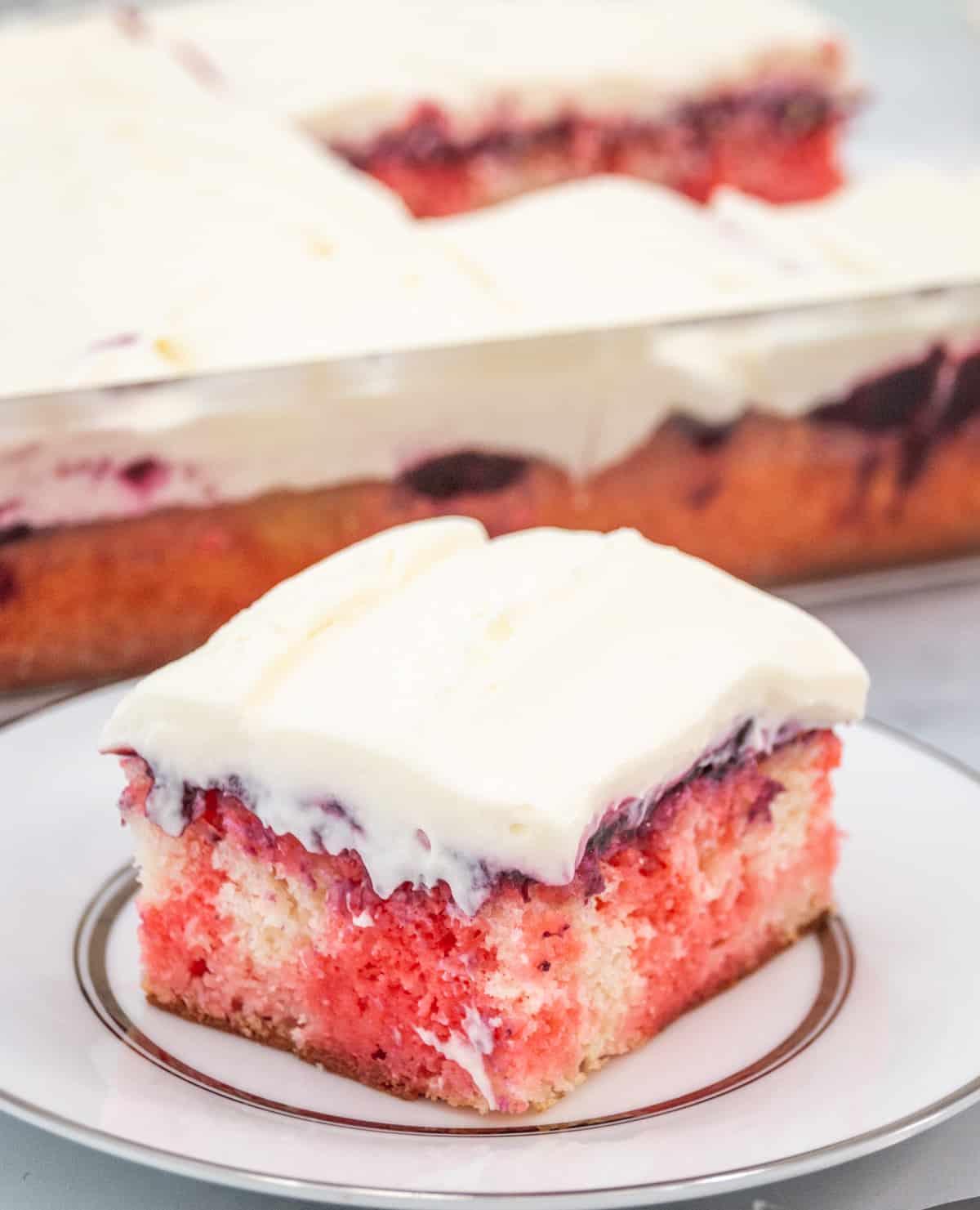 berry poke cake slice on a white plate