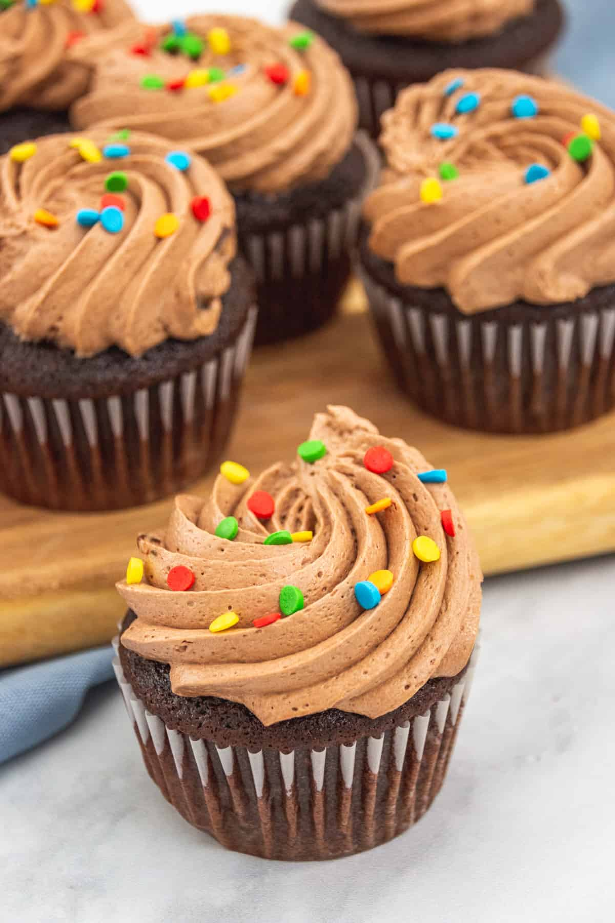 chocolate cupcakes on a wooden board with sprinkles and icing