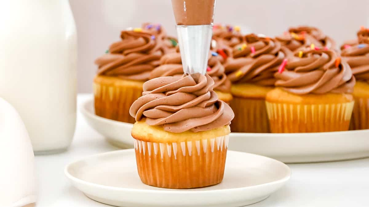 piping chocolate cream cheese frosting on a cupcake